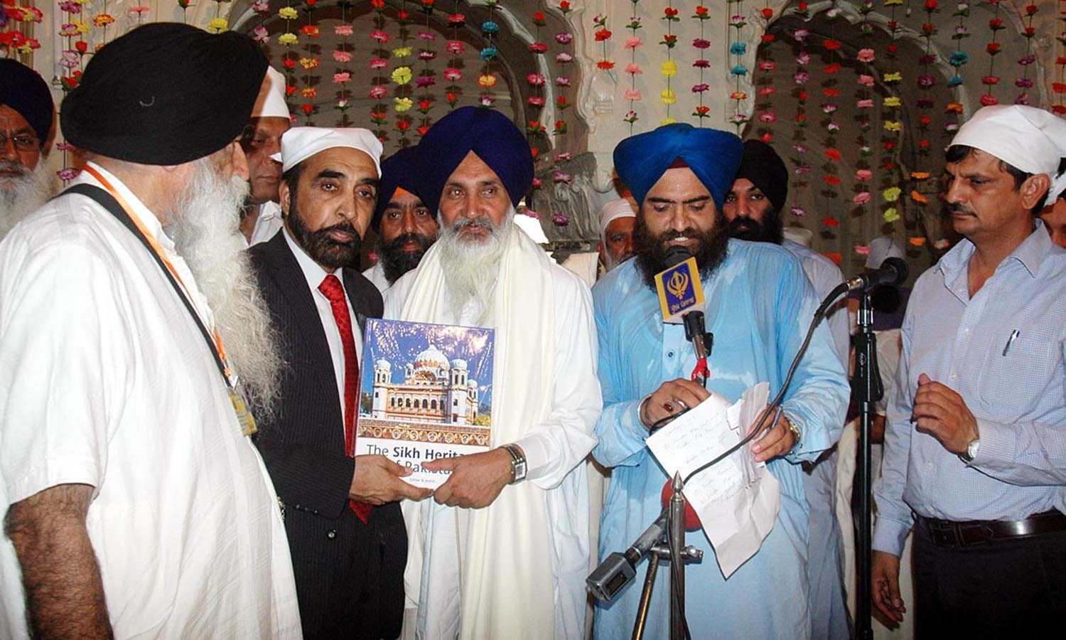 Chairman Evacuee Trust Property Board Siddiq ul Farooq presenting a book The Sikh Heritage of Pakistan to Leader of delegation of Indian Sikh Pilgrims, Ram Paul Singh at Dera Sahab.